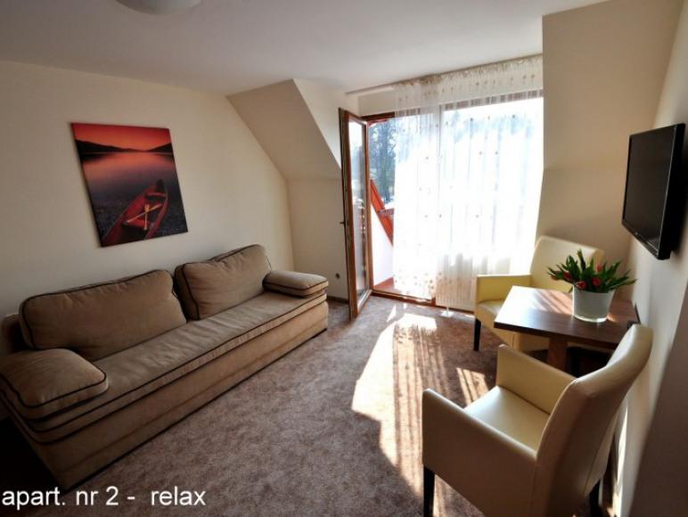 apartament nr 2 relax z wersalką, stolikiem z fotelami i telewizor.