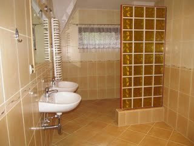 azienka z umywalkami, kabiną prysznicową i WC