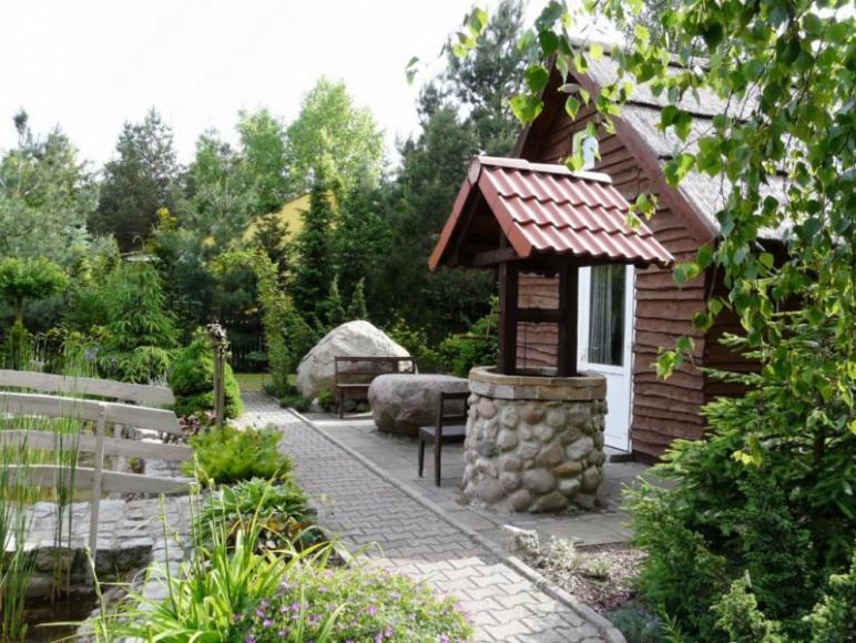 wejście do domku, stół kamienny i imitacja studni