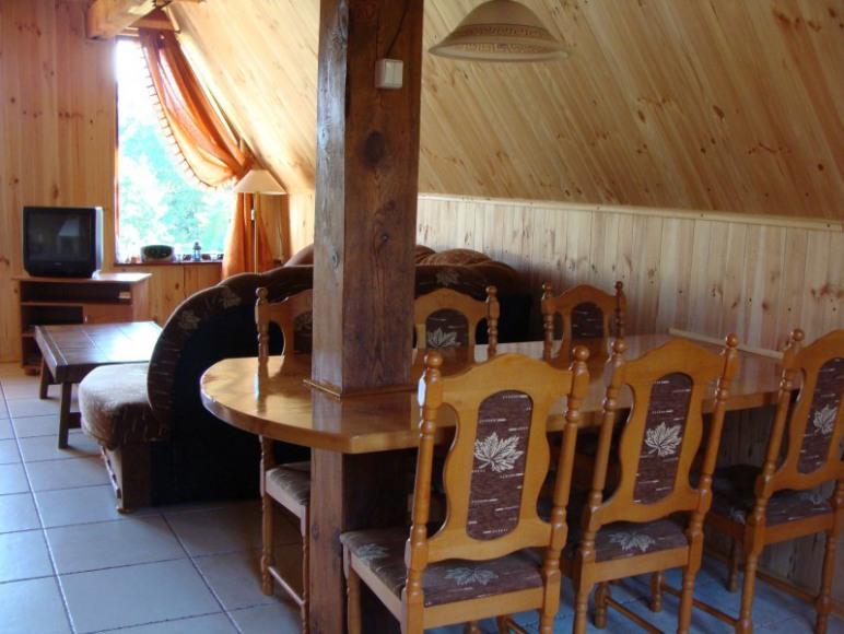 Stół i widok na część rekreacyjną w domku drewnianym