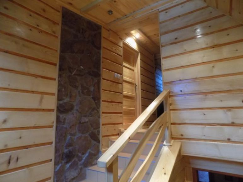 Klatka schodowa wykończona w drewnie i kamieniu.