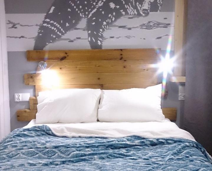 Sypialnia z ręcznie malowanym muralem z rozleniwionym niedźwiedziem.