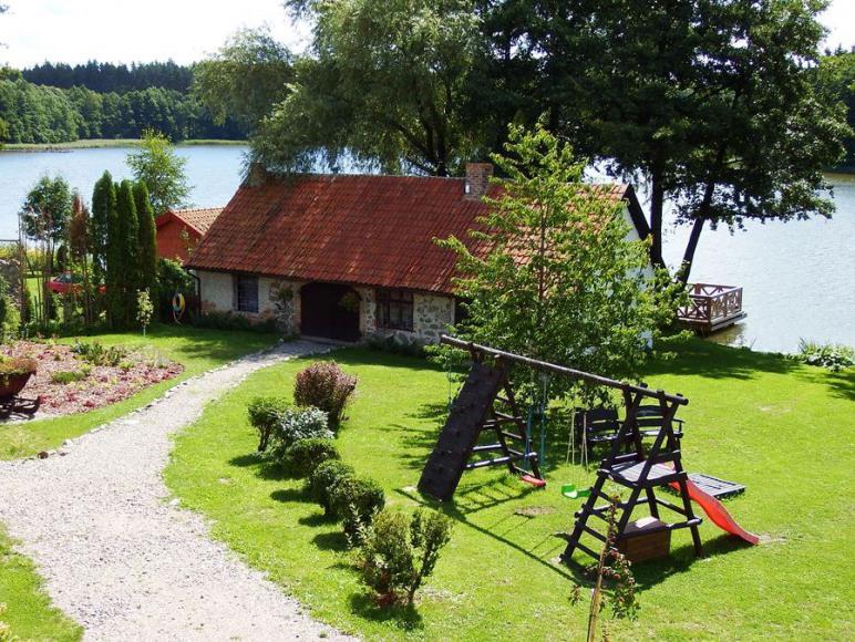 Widok z balkonu na kuźnię, jezioro i las.