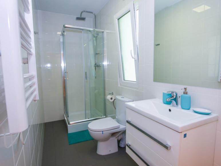 Duża łazienka z prysznicem, toaletą i umywalką z dużym lustrem