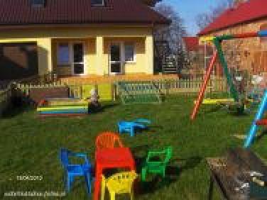 plac zabawa i budynek z pokojami 2-,3- osobowymi i studio