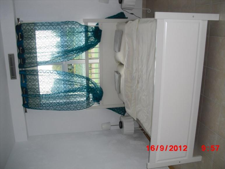 pokój z dużym łóżkiem i łazienką