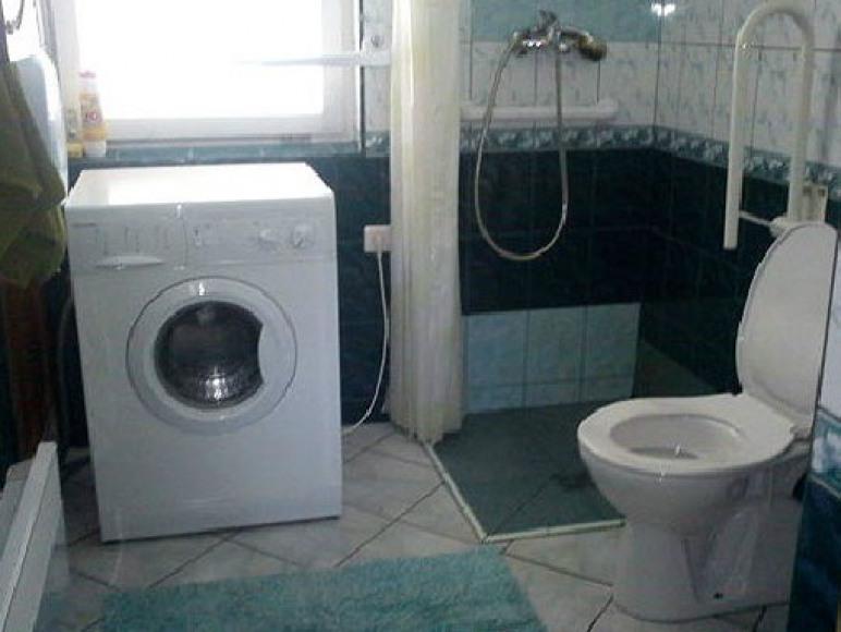 łazienka z ubikacją, kabiną prysznicową, umywalką i pralką